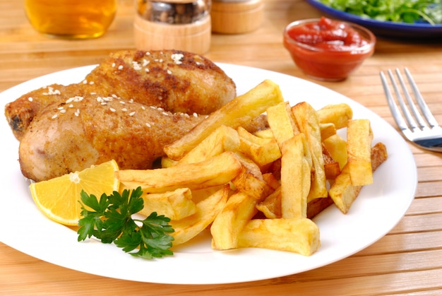 Gebratene hähnchenschenkel mit zitronen-kartoffel-chips auf weißem teller