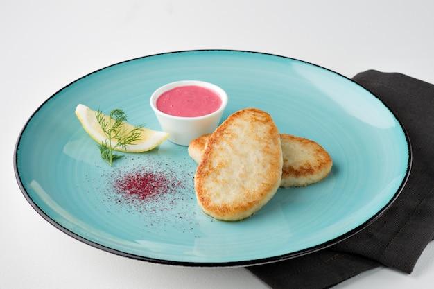 Gebratene hechtkoteletts mit zitrone, vendure und rosa sauce auf türkisfarbenem teller und schwarzer serviette auf weißem hintergrund