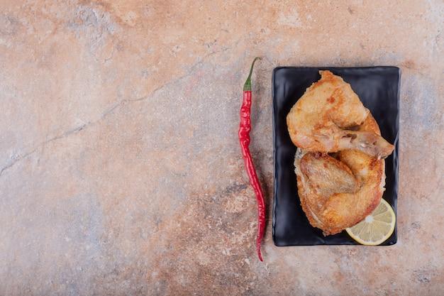 Gebratene hühnchenstücke mit scharfen chilischoten.