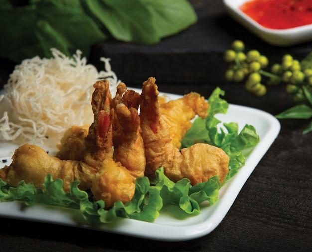 Gebratene hühnerbeine dienten mit reisspaghettis und grünem salat in einer weißen platte