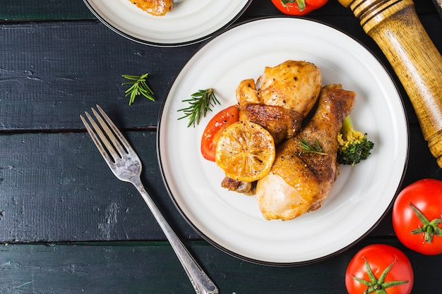 Gebratene hühnerbeine mit gemüse und kräutern