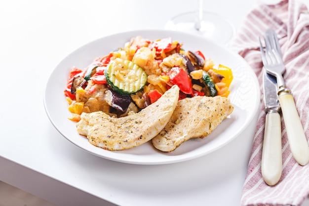 Gebratene hühnerbrust mit gegrillter zucchini, auberginen und rotem und gelbem paprika auf weißem teller mit weinglas.