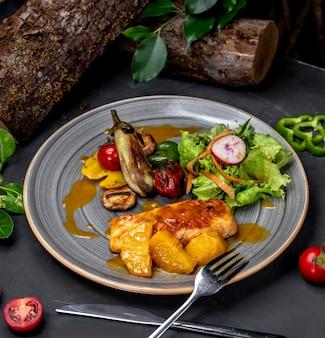 Gebratene hühnerbrust mit gemüse und obst
