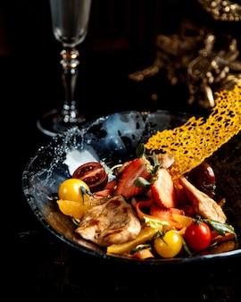 Gebratene hühnerbrust mit geschnittenem obst und gemüse