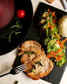 Gebratene hühnerbrust serviert mit salat und reis