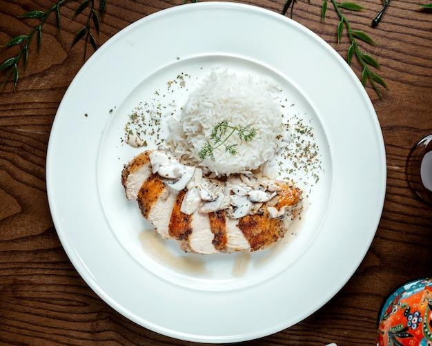 Gebratene hühnerbrust unter pilzsauce mit reis