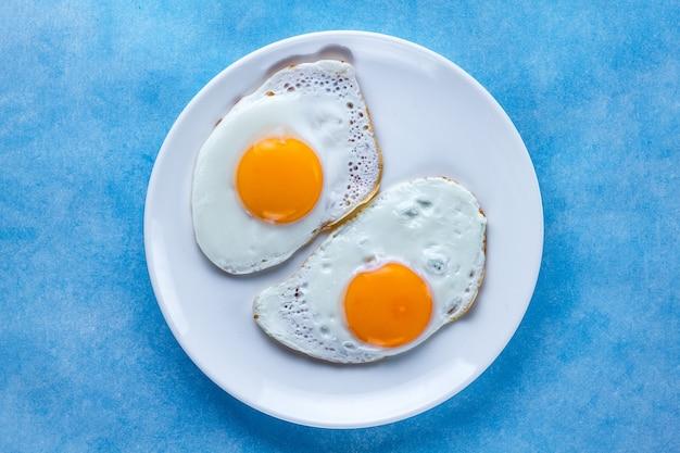 Gebratene hühnereien auf einer platte zum ein gesundes frühstück auf einer blauen brandung. protein essen. ansicht von oben