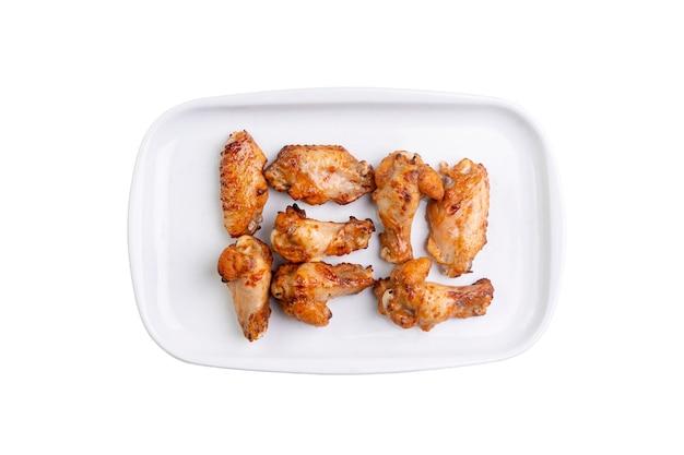 Gebratene hühnerflügel auf weißem teller isoliert.