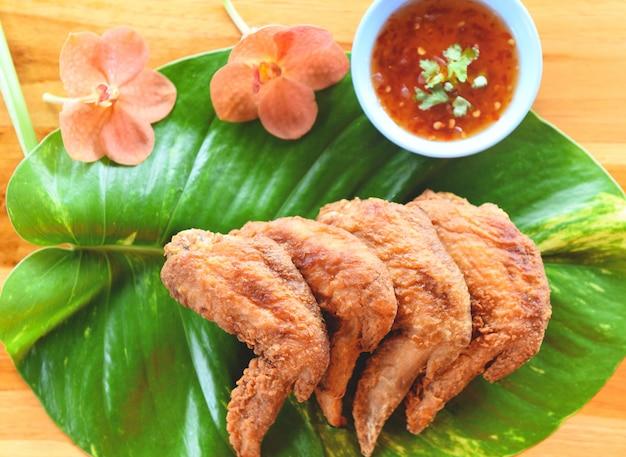 Gebratene hühnerflügel dienten auf blättern mit knusperigen hühnerflügeln der draufsicht der soße auf holztisch