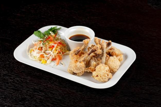 Gebratene hühnerflügel, garniert mit frischem gemüse und teriyaki-sauce
