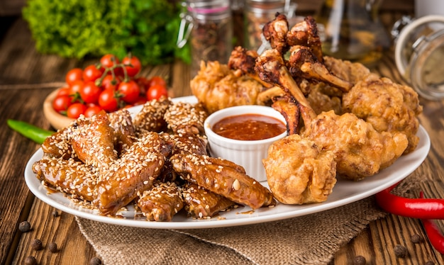 Gebratene hühnerflügel im teig mit ketchup und sauce