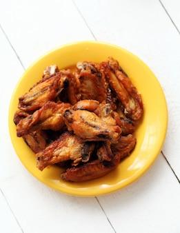 Gebratene hühnerflügel in einer gelben schüssel