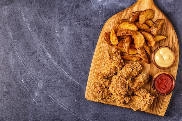 Gebratene hühnerflügel mit gebratenen kartoffelscheiben