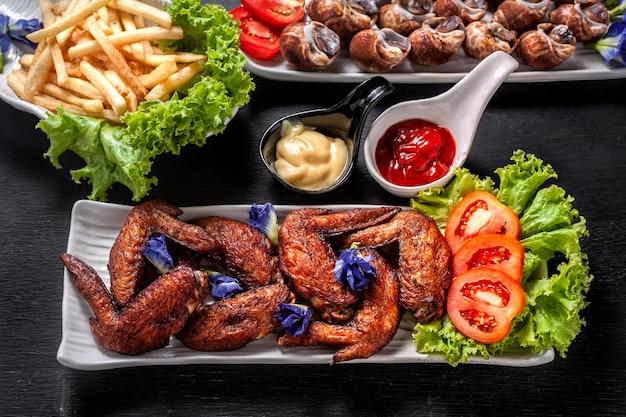 Gebratene hühnerflügel mit gestreamtem babylon und pommes frites