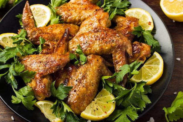 Gebratene hühnerflügel mit petersilie und zitrone
