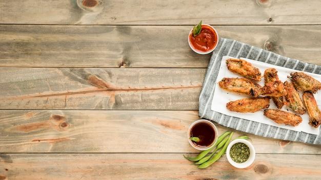 Gebratene hühnerflügel mit verschiedenen pikanten saucen