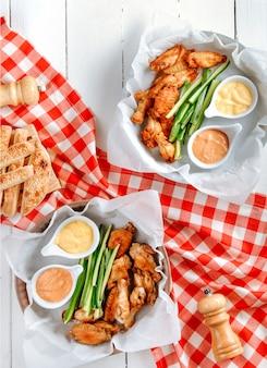 Gebratene hühnerflügel mit verschiedenen saucen