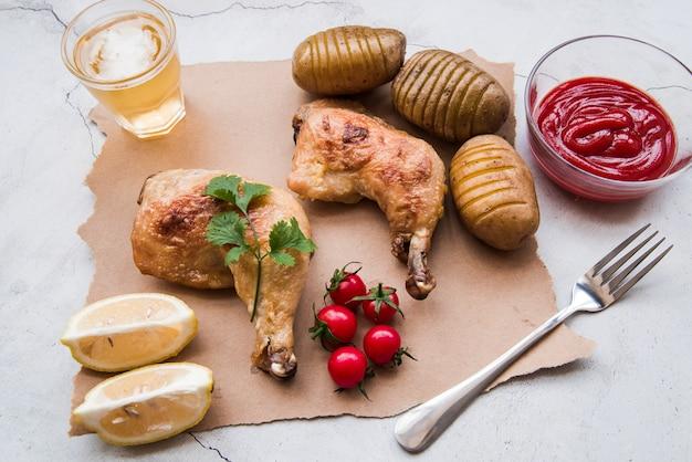 Gebratene hühnerkeule; gekochte kartoffel; soße; kirschtomate; zitrone; gabel und bier zum abendessen auf verwittertem hintergrund