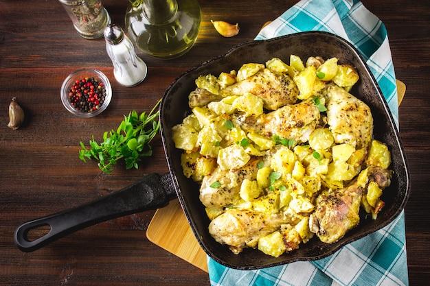 Gebratene hühnerkeule mit kartoffeln mit kümmel und knoblauch.
