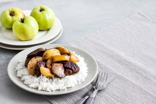 Gebratene hühnerleber mit äpfeln serviert mit weißem reis auf einem teller.