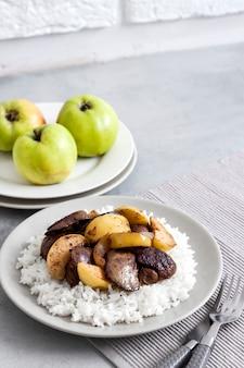Gebratene hühnerleber mit äpfeln serviert mit weißem reis auf einem teller