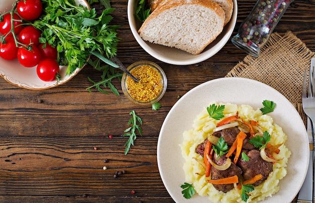 Gebratene hühnerleber mit gemüse und beilage aus kartoffelpüree. gesundes essen. ansicht von oben.