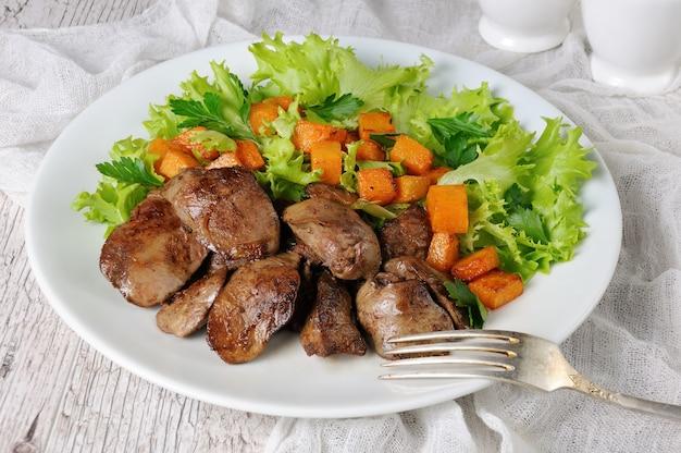 Gebratene hühnerleber mit gemüsebeilage, gebackener kürbis in salatblättern