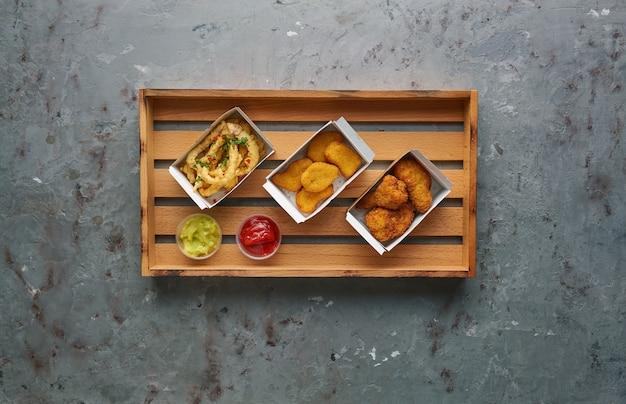 Gebratene hühnernuggets mit beinen und knusprigem tintenfisch auf holztablett, draufsicht, kopierraum. street food-konzept