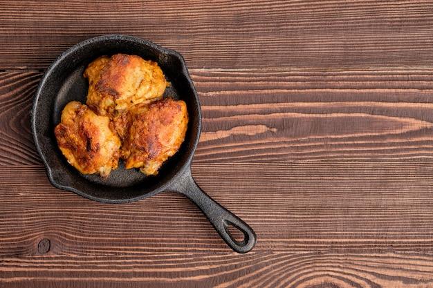 Gebratene hühnerschenkel in der roheisenbratpfanne