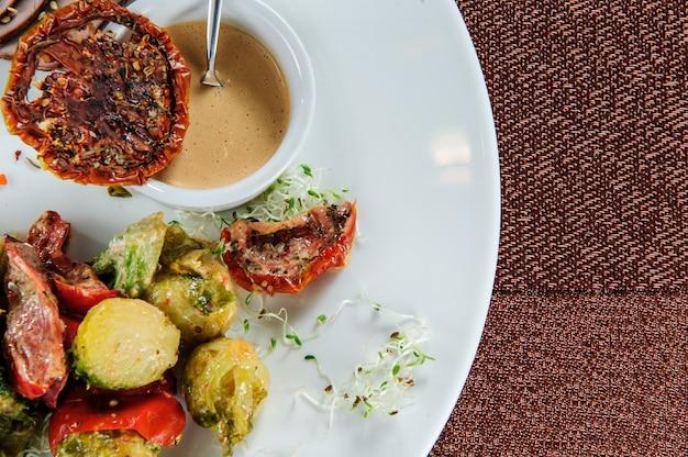 Gebratene kabeljaufiletsröllchen serviert mit hirse und gedünstetem brokkoli, karotte, rosenkohl und zucchini