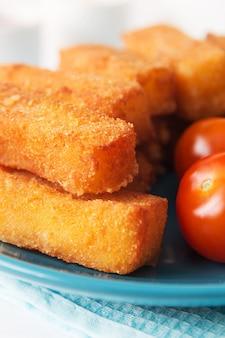 Gebratene käsestöcke mit tomaten auf einer blauen platte
