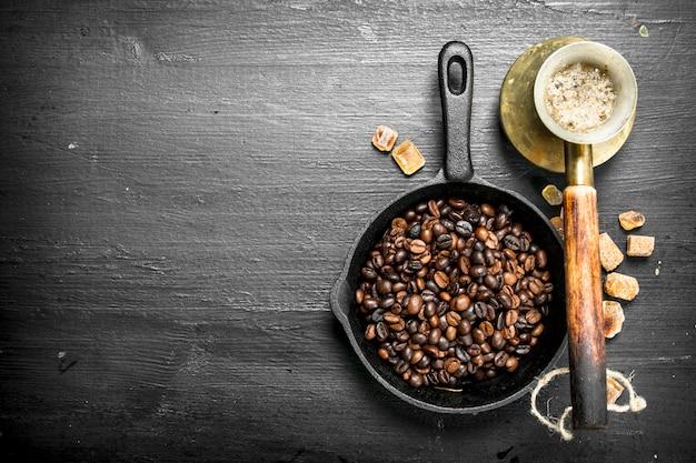 Gebratene kaffeebohnen in einer pfanne. auf der schwarzen tafel.