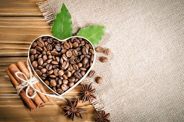 Gebratene kaffeebohnen liegen in form eines herzens auf holzbrettern und sackleinen.