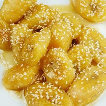 Gebratene karamellisierte süße kochbananen. dominikanisches essen. reife kochbananen karamellisiert mit butter und sesam, typisches rezept aus einigen karibischen ländern. es wird wegerich in versuchung oder schurke genannt