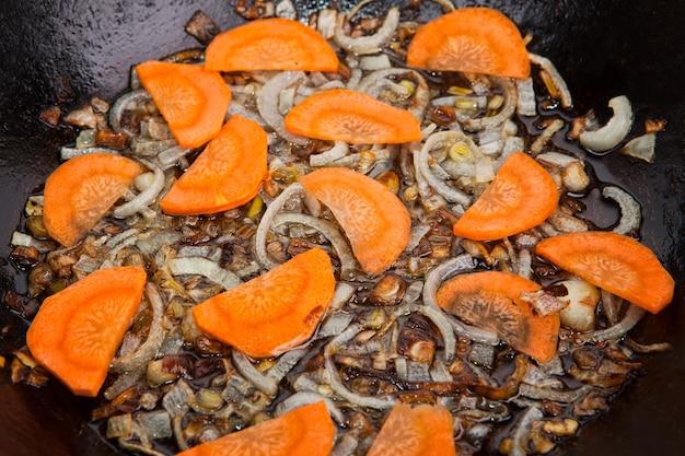 Gebratene karotten und zwiebeln auf der bratpfanne hautnah