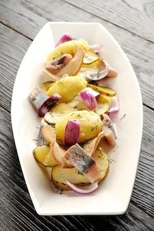 Gebratene kartoffel und eingelegter hering mit zwiebeln und brotchips