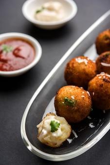 Gebratene kartoffelkäsebällchen oder kroketten mit tomatenketchup. selektiver fokus