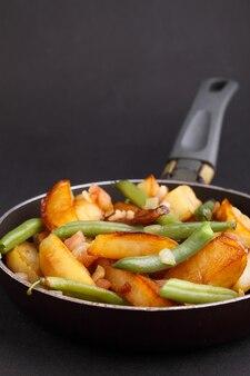 Gebratene kartoffeln mit grünen bohnen und speck in einer pfanne