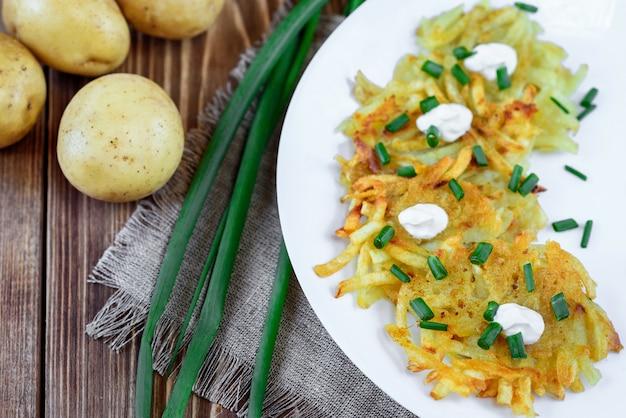 Gebratene kartoffelpuffer oder draniki mit sauerrahm und frühlingszwiebeln. das nationalgericht von belarus, der ukraine und russland.