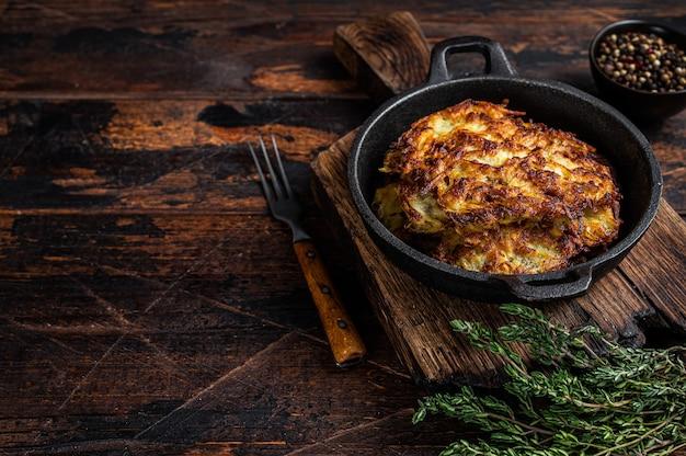 Gebratene kartoffelpuffer oder krapfen mit kräutern in einer pfanne. dunkler holztisch. draufsicht.