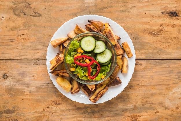 Gebratene kartoffelscheibe und frischgemüse in der schüssel auf weißer platte