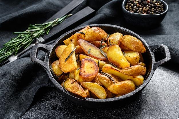 Gebratene kartoffelschnitze, pommes frites in einer pfanne. schwarzer hintergrund. draufsicht