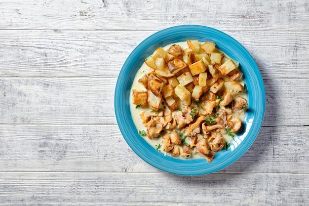Gebratene kartoffelstücke serviert mit pfifferlingsauce auf blauem teller, horizontale ansicht von oben, flach, freier raum
