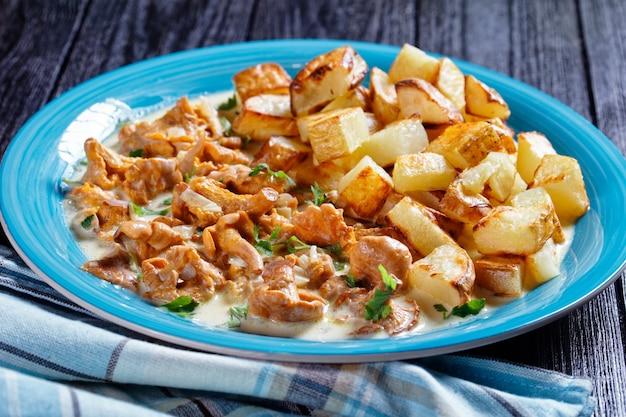 Gebratene kartoffelstücke serviert mit pfifferlingsauce auf blauem teller, horizontale ansicht von oben, nahaufnahme
