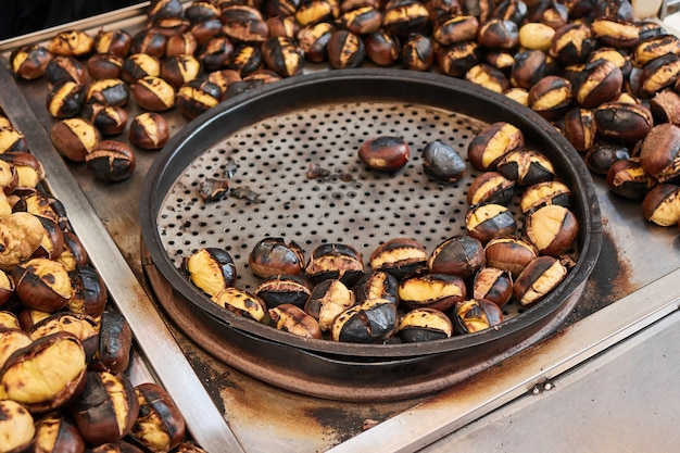 Gebratene kastanien auf der straße. straßenessen. geröstete kastanien werden in einer speziellen perforierten kastanienpfanne serviert.