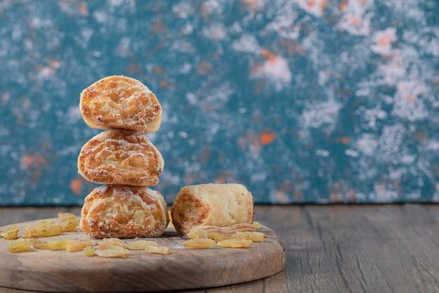Gebratene kekse mit gelben rosinen und zuckerpulver auf der oberseite.