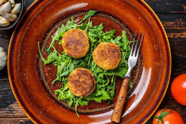 Gebratene kichererbsen-falafel-pastetchen mit rucola auf einem teller. dunkler holztisch. draufsicht.