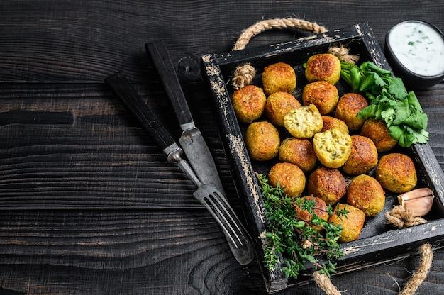 Gebratene kichererbsen-falafelbällchen mit knoblauch-joghurt-sauce in einem holztablett