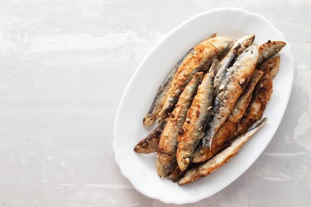 Gebratene kleine sardinen auf weißer schale auf keramiktisch