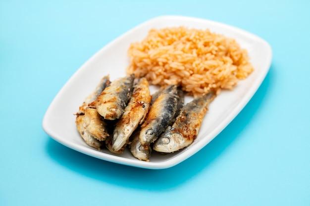 Gebratene kleine sardinen mit tomatenreis auf weißem teller auf blauem tisch